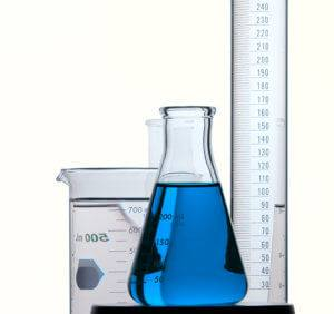A flask is filled with blue liquid amidst other lab materials.
