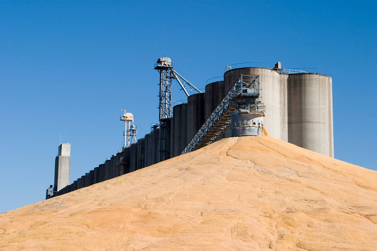 A feed mill system stands against a blue sky.