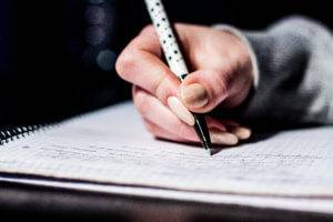 A hand writes on a notebook with a pen.